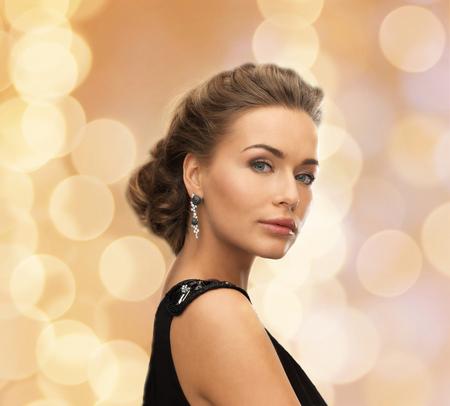 mujer elegante: personas, días de fiesta, navidad y el concepto de glamour - hermosa mujer en traje de noche que llevan pendientes sobre fondo de luces de color beige