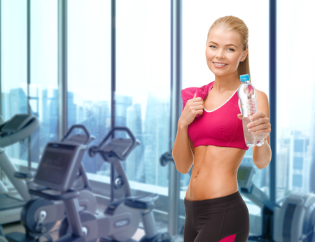 fitness gym: people, sport, fitness and recreation concept - happy woman with bottle of water and towel over gym machines background Stock Photo