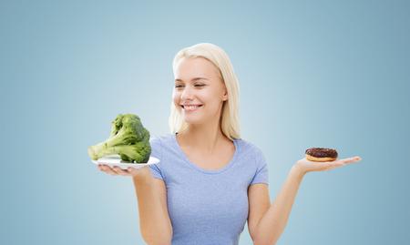 alimentación saludable, la comida chatarra, la dieta y el concepto de elección de personas - la mujer sonriente que elige entre el brócoli y la rosquilla sobre fondo azul