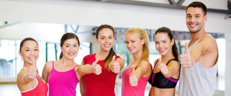 manos juntas: fitness, deporte, entrenamiento, gimnasio y estilo de vida concepto - grupo de gente feliz en el gimnasio que muestra los pulgares para arriba Foto de archivo