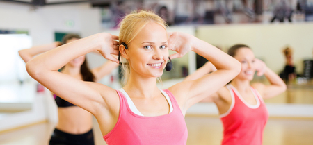 mics: fitness, sport, training, gym and lifestyle concept - group of smiling people with trainer exercising in the gym