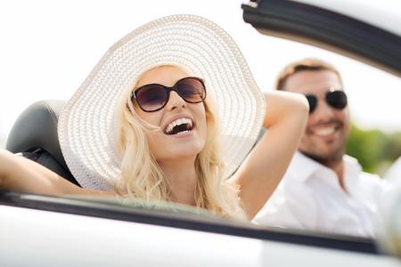 Verkehr, Freizeit, Autoreise und Menschen Konzept - glücklicher Mann und Frau in Cabrio Auto fahren im Freien Standard-Bild