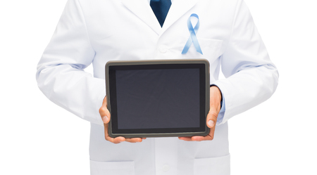 urologist: healthcare, people and medicine concept - close up of smiling male doctor hands with sky blue prostate cancer awareness ribbon holding tablet pc computer Stock Photo