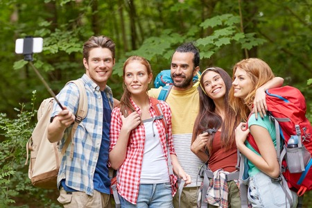 young friends: technology, travel, tourism, hike and people concept - group of smiling friends walking with backpacks taking picture by smartphone on selfie stick in woods