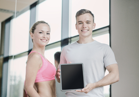 ropa deportiva: fitness, sport, advertising, technology and diet concept - smiling young woman and personal trainer with tablet pc blank screen in gym