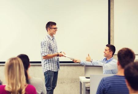 profesor alumno: la educación, la escuela secundaria, la tecnología y el concepto de la gente - sonriendo estudiante con el bloc de notas, ordenador portátil que se coloca delante del profesor muestra los pulgares para arriba gesto en el aula Foto de archivo