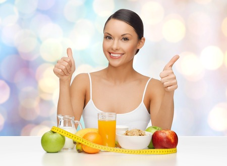 people, gesture and diet concept- happy asian woman with healthy food showing thumbs up over blue lights background