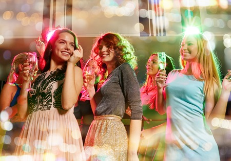 holidays: party, holidays, celebration, nightlife and people concept - smiling friends with glasses of champagne dancing in club