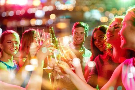 partito, feste, celebrazioni, vita notturna e la gente concept - amici sorridenti tintinnano bicchieri di champagne e birra in centro