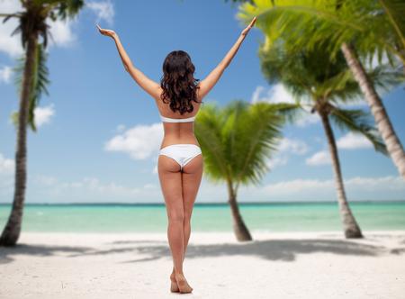Menschen, Mode, Schönheit, Sommer und Reise-Konzept - junge Frau im weißen Bikini Badeanzug mit erhobenen Händen aus zurück über tropischen Strand mit Palmen Hintergrund aufwirft