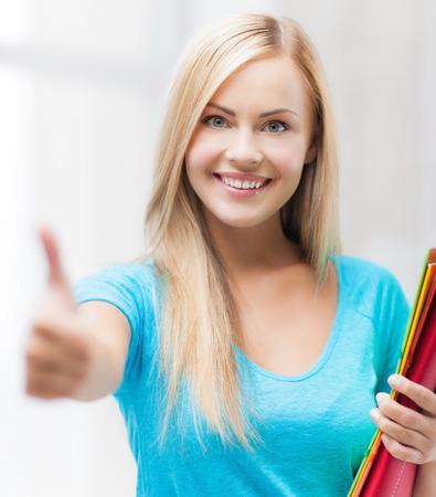 carpeta: foto del estudiante sonriente con las carpetas que muestra los pulgares para arriba Foto de archivo