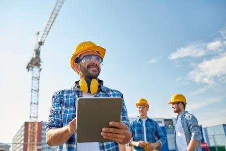 negocio, la construcción, la industria, la tecnología y el concepto de la gente - constructor sonriente en el casco con el equipo de PC de la tablilla sobre grupo de constructores en el emplazamiento de la obra Foto de archivo