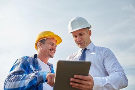 tecnología informatica: negocio, construcción, trabajo en equipo, la tecnología y el concepto de la gente - sonriendo constructores de cascos con ordenador Tablet PC al aire libre Foto de archivo