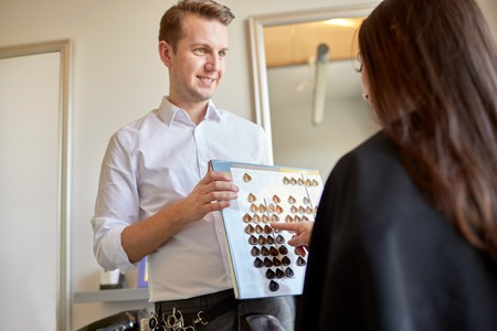 dyeing: beauty, hair dyeing and people concept - happy young woman with hairdresser choosing hair color from palette samples at salon Stock Photo