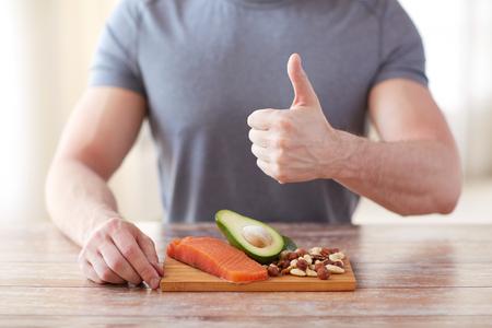 gesunde Ernährung, Diät, Gestik und Menschen Konzept - in der Nähe der männlichen Hände up auf Schneidebrett auf dem Tisch Daumen nach oben mit Lebensmittel reich an Protein zeigen