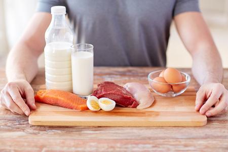 スポーツ、フィットネス、健康的なライフ スタイル、食事、人々 の概念 - テーブルにまな板の上のタンパク質の豊富な食品と男性の手のクローズ