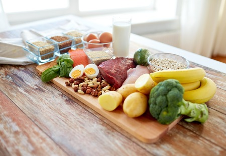 cutting meat: balanced diet, cooking, culinary and food concept - close up of vegetables, fruit and meat on wooden table