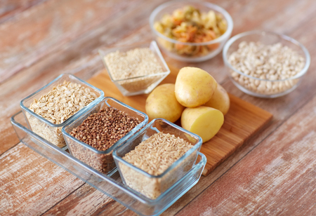 carbohydrate: diet, cooking, culinary and carbohydrate food concept - close up of grain, cereals in glass bowls and potatoes on table