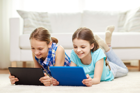 kids playing video games: people, children, technology, friends and friendship concept - happy little girls with tablet pc computers lying on floor at home