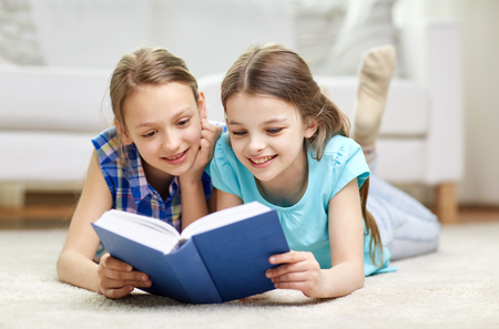 people, children, friends, literature and friendship concept - two happy girls lying on floor and reading book at home Stock Photo