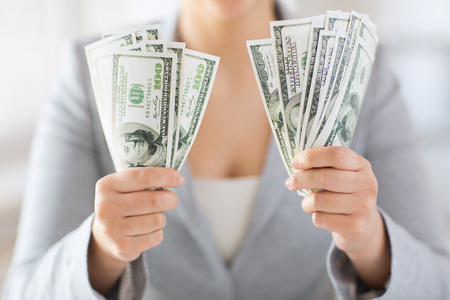 american banker: business, finance, saving, banking and people concept - close up of woman hands holding us dollar money