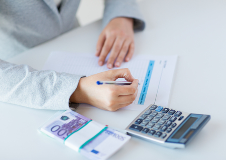finance report: business, finance, tax and people concept - close up of woman hands counting euro money with calculator and tax report form