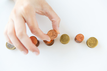 money stack: business and money saving concept - close up of female hand putting euro coins into columns in office Stock Photo