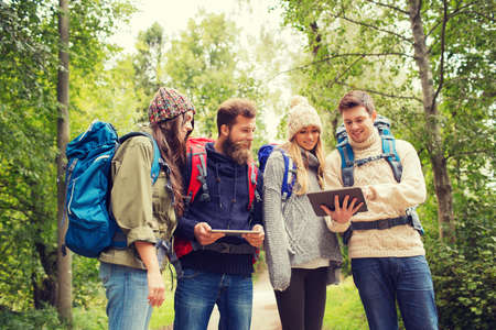 a beard: adventure, travel, tourism, hike and people concept - group of smiling friends with backpacks and tablet pc computers outdoors