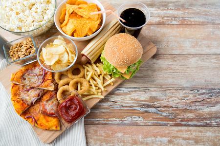 패스트 푸드와 건강에 해로운 먹는 개념 - 가까운 나무 테이블에 패스트 푸드 스낵과 코카콜라 음료의 최대 스톡 콘텐츠