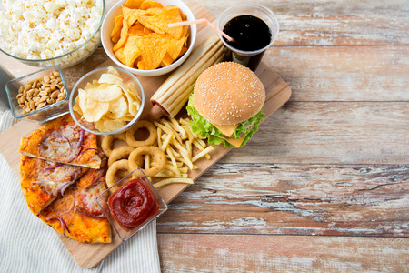 botanas: comida rápida y el concepto de alimentación poco saludable - cerca de bocadillos de comida rápida y bebidas Coca Cola en la mesa de madera