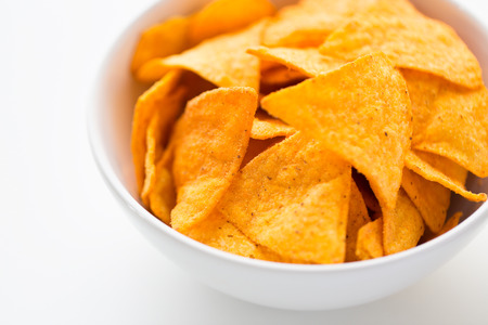 crisps: food, junk-food, cuisine and eating concept - close up of corn crisps or nachos in bowl