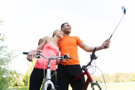 summer sport: fitness, sport, people, technology and healthy lifestyle concept - happy couple with bicycle taking picture by smartphone on selfie stick outdoors Stock Photo