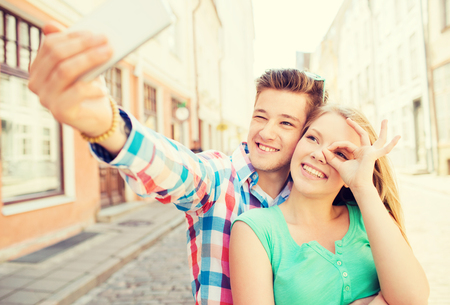 happy couple: travel, vacation, technology and friendship concept - smiling couple with smartphone in city