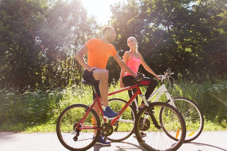 family in park: fitness, sport, people and healthy lifestyle concept - happy couple riding bicycle outdoors at summer