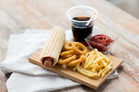 hot drink: fast food and unhealthy eating concept - close up of deep-fried squid rings, french fries, coca cola and ketchup on wooden table Stock Photo