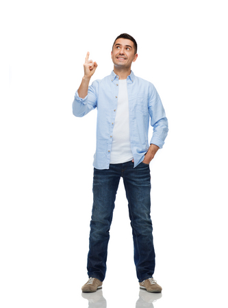 isolated man: happiness, gesture and people concept - smiling man pointing finger up Stock Photo