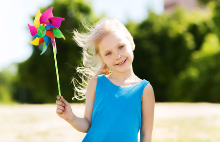 5 6 years: summer, childhood, leisure and people concept - happy little girl with colorful pinwheel toy outdoors Stock Photo