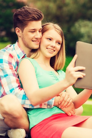 couples in love: vacation, holidays, technology and friendship concept - smiling couple with tablet pc computer making selfie in park