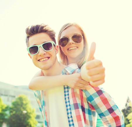 teen love: summer holidays, vacation, love, gesture and friendship concept - smiling teen couple in sunglasses having fun and showing thumbs up in park Stock Photo