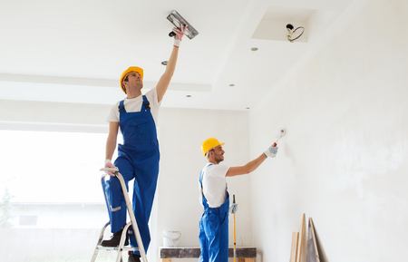 professional: business, building, teamwork and people concept - group of builders in hardhats with plastering tools indoors