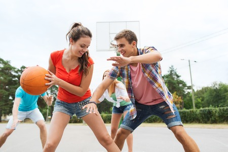 teen: summer vacation, sport, games and friendship concept - group of happy teenagers playing basketball outdoors
