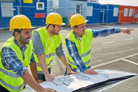 team building: building, construction, development, teamwork and people concept - close up of builders in hardhats and high visible vests with blueprint on car hood Stock Photo