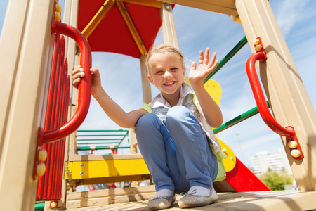 climbing frame: summer, childhood, leisure, gesture and people concept - happy little girl waving hand on children playground climbing frame Stock Photo