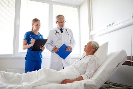 sick room: medicine, age, health care and people concept - doctor and nurse with clipboards visiting senior patient woman at hospital ward Stock Photo