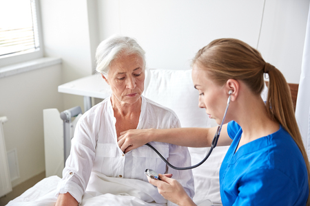cardiologist: medicine, age, support, health care and people concept - doctor or nurse with stethoscope visiting senior woman and checking her breath or heartbeat at hospital ward