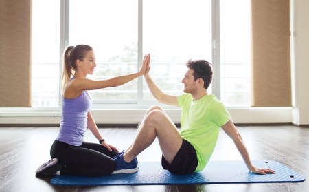 man sit: fitness, sport, training, teamwork and people concept - happy man with personal female trainer doing sit ups and high five gesture in gym Stock Photo