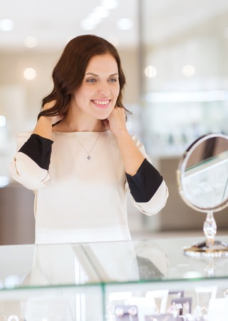 reflection mirror: sale, consumerism, shopping and people concept - happy woman choosing and trying on pendant at jewelry store Stock Photo