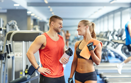professional woman: sport, fitness, lifestyle and people concept - smiling man and woman with protein shake bottle and towel talking in gym