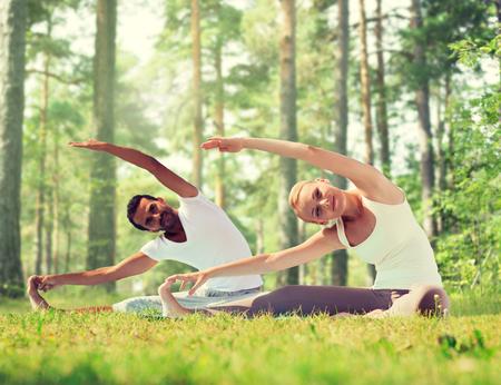 Fitness, Sport, Yoga und Menschen Konzept - glückliche Paar Stretching auf Matten über grünen Wald Hintergrund