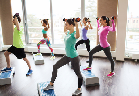 woman working out: fitness, sport, aerobics and people concept - group of smiling people working out with dumbbells flexing muscles on step platforms in gym